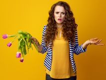 Woman on yellow background with wilted flowers. Unhappy trendy woman with long wavy brunette hair on yellow background with wilted flowers Stock Images