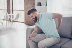 Unhappy troubled stylish red bearded man suffering from strong p. Ain in back and can`t call to the ambulance, on the sofa at home royalty free stock image