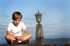 Unhappy Tween. An unhappy young elementary aged tween boy sitting on a high wall, blue cloudy sky and decorative street light in background. Shallow depth of Stock Photography