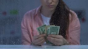 Unhappy unemployed middle-aged woman holding dollar cash, lack of money, poverty stock video