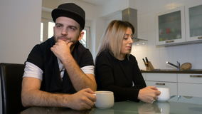 Unhappy upset couple having morning coffee not talking to each other after a fight stock footage