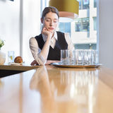 Unhappy waitress at work. Fed up waitress at work. She has her eyes closed and is resting her head on her hand at the bar, with a tray of dirty glasses in front Stock Image