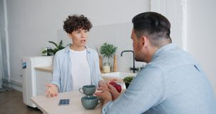 Unhappy wife fighting with husband during breakfast in kitchen talking gesturing. Unhappy wife beautiful young lady is fighting with sad husband during breakfast stock footage