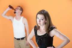 Unhappy Wife with Drunk Husband. Unhappy Caucasian wife with alcoholic husband on orange background stock photo