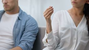 Unhappy wife holding engagement ring in hand, upset husband nearby, divorce risk. Stock footage stock footage