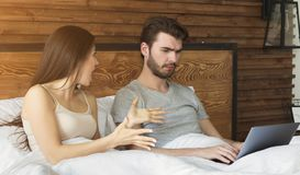 Woman arguing with man, addicted to internet stock image