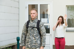 Unhappy Wife Waving Goodbye To Male Soldier. Unhappy Young Wife Waving Goodbye To Male Soldier Outside House Stock Images