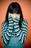 Unhappy Woman. Portrait of a serious woman wearing a long sleeved sweater, with her hands flat against each side of her face.  Sad expression.  Isolated on Royalty Free Stock Images