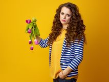 Unhappy woman against yellow background showing wilted flowers. Unhappy trendy woman in striped jacket against yellow background showing wilted flowers Stock Photography