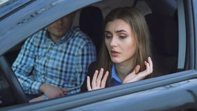 Unhappy woman arguing in car, while man calms her in 4K.  stock video footage