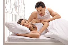 Unhappy woman in bed with concerned guy comforting her Royalty Free Stock Photography