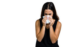 Unhappy woman blowing nose. Against white background Royalty Free Stock Photography