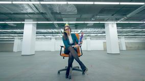 Unhappy woman blows a cracker, sitting in an office chair. 4K stock video footage