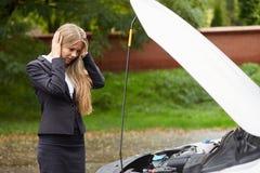 Unhappy woman with a broken car. Unhappy business woman with a broken car Stock Image