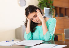 Unhappy woman calculating home Royalty Free Stock Image