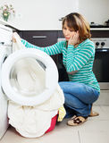 Unhappy woman cheking  clothes near washing machine Stock Photography