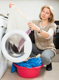 Unhappy woman cheking white clothes near washing machine Stock Images
