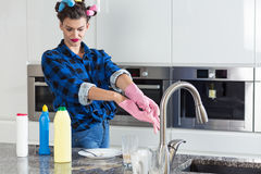 Unhappy woman cleaning big kitchen Stock Photo