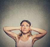 Unhappy woman covering her ears looking up stop making loud noise Royalty Free Stock Photos