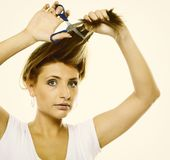 Unhappy woman cutting her hair with scissors Royalty Free Stock Photos