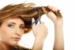 Unhappy woman cutting her hair with scissors isolated Stock Photography