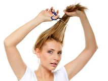Unhappy woman cutting her hair with scissors Stock Image