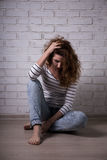 Unhappy woman with depression or headcahe sitting on the floor o Royalty Free Stock Photos