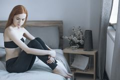 Unhappy woman with depression. Sitting alone on bed with anorexia problem Royalty Free Stock Photos