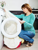 Unhappy  woman doing laundry with washing machine Royalty Free Stock Images