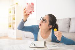 Unhappy woman emptying her piggybank. Young unhappy woman emptying her piggybank savings with less than expected sitting on sofa in the living room at home royalty free stock photo