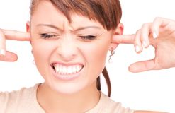 Unhappy woman with fingers in ears. Picture of unhappy woman with fingers in ears Royalty Free Stock Photos
