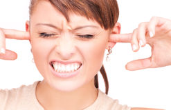 Unhappy woman with fingers in ears Royalty Free Stock Images