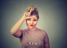 Unhappy woman giving loser sign on forehead, looking at you, disgust on face. Closeup portrait young unhappy woman giving loser sign on forehead, looking at you Royalty Free Stock Image