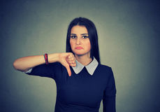Unhappy woman giving thumb down gesture looking with disapproval stock images