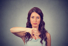 Unhappy woman giving thumbs down gesture looking with negative expression and disapproval. Beautiful cute young woman on gray wall background Stock Photography