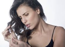 Unhappy woman and hairstyle. Portrait of a pretty woman watching  her split ends with a frustrated expression on face Stock Photography