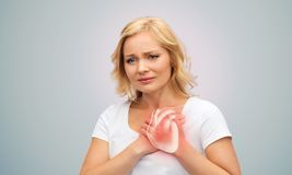 Unhappy woman having heart attack or heartache. People, healthcare and health problem concept - unhappy middle-aged woman having heart attack or heartache over stock image