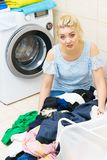 Unhappy woman having a lot of laundry royalty free stock photography