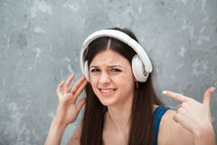 Unhappy woman with headphones. Unhappy woman with wireless headphones royalty free stock photography