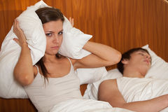 Unhappy woman and her snoring husband. Unhappy woman and her snoring husband in bedroom Stock Photos