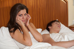 Unhappy woman and her snoring husband. Stock Photography