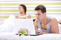 Unhappy woman because his husband working in bed Stock Images