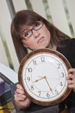 Unhappy woman holding big watch Stock Images