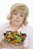 Unhappy Woman Holding Bowl Of Salad. Portrait of unhappy mature women holding bowl of vegetable salad over white background Royalty Free Stock Images