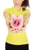 Unhappy woman holding piggybank. Stock Photo