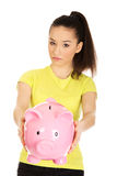 Unhappy woman holding piggybank. Royalty Free Stock Image
