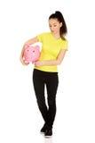 Unhappy woman holding piggybank. Royalty Free Stock Photography