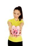 Unhappy woman holding piggybank. Stock Image