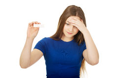 Unhappy woman holding pregnancy test. Royalty Free Stock Photo