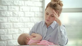 Unhappy woman holding sleeping baby on hands. Stress mother concept